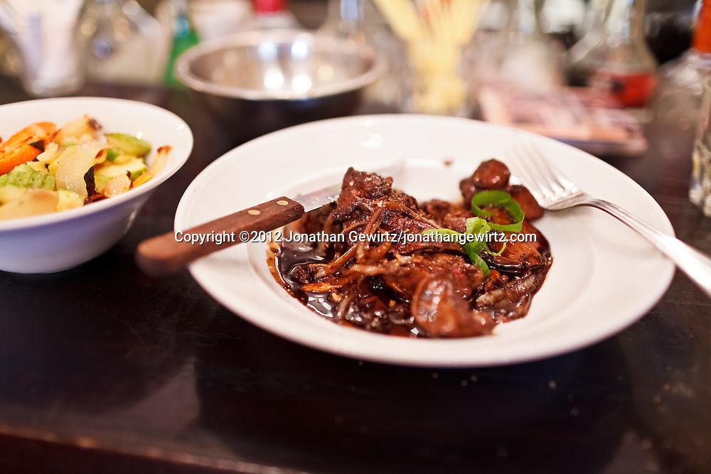 A plate of cooked liver and onions on the bar at a stylish restaurant. WATERMARKS WILL NOT APPEAR ON PRINTS OR LICENSED IMAGES.
