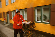 A postman delivers mail in the old Nyboder neighborhood in Copenhagen, Denmark