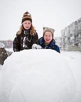 Systkinin úti að búa til snjókarl á aðfangadag.