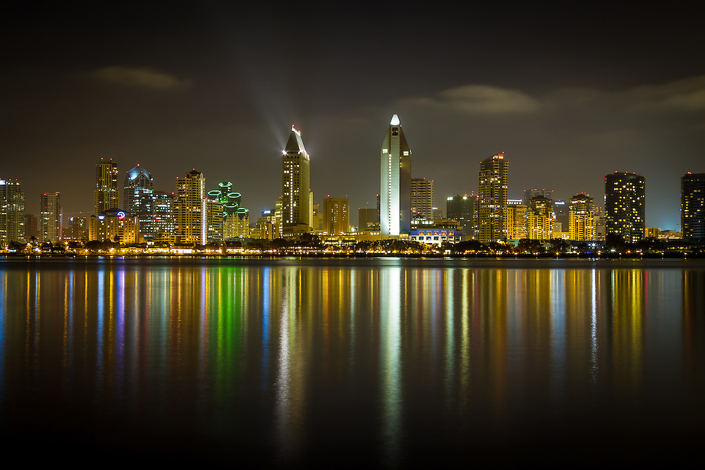 The downtown San Diego city skyline lights up the bay and water at night. Viewed from Coronado.