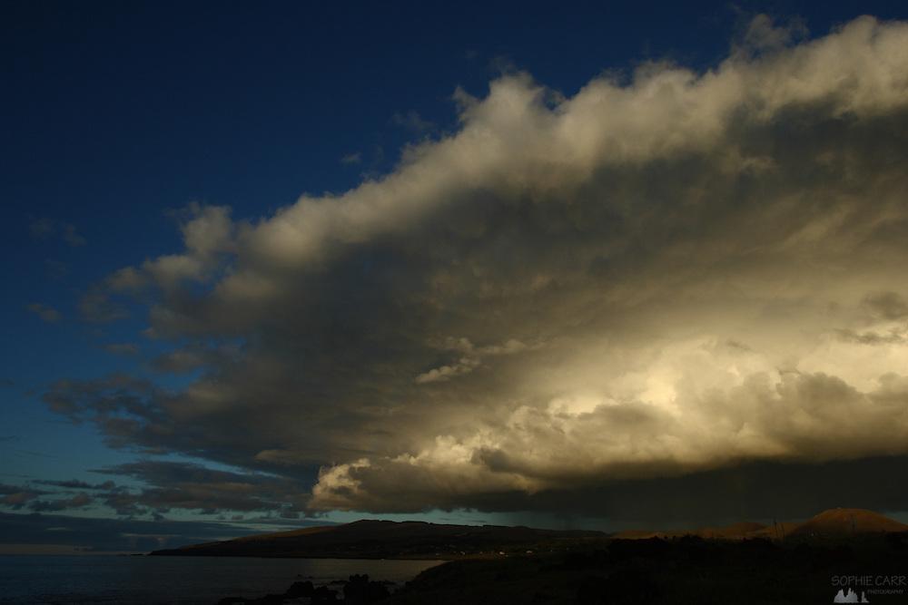 A big storm cloud builds over Hanga Roa on Easter Island's south-western coast