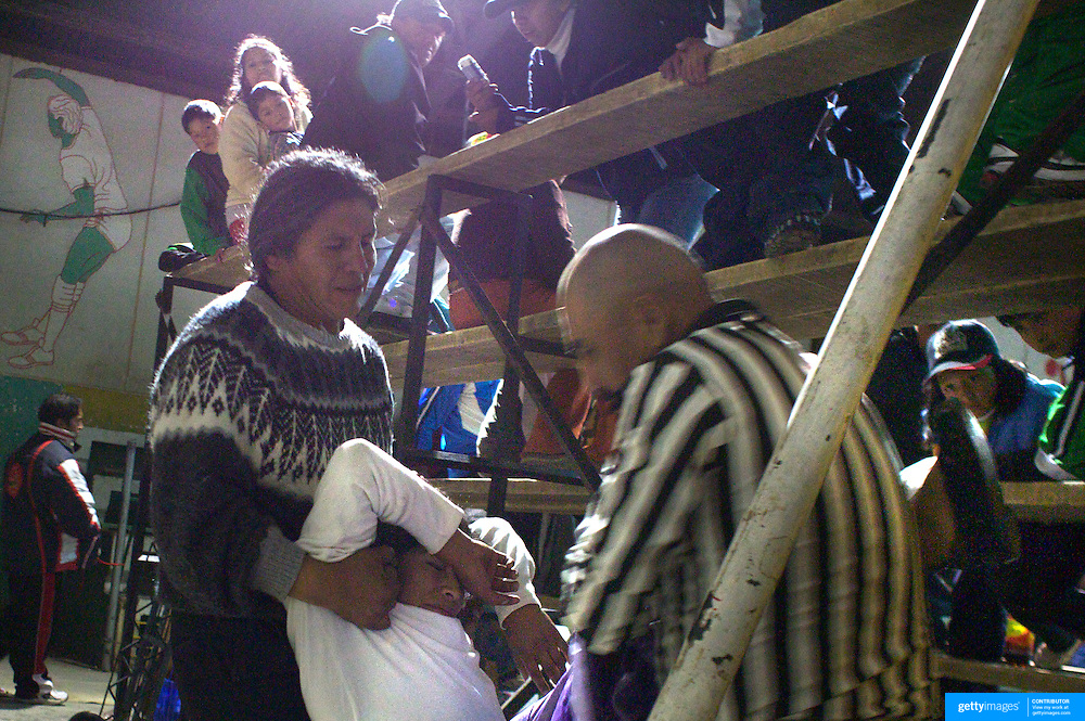 Cholita Yolanda La Amorosa is carried from the ring after being knocked unconscious by her male opponent during the 'Titans of the Ring' wrestling group performance at El Alto's Multifunctional Centre. Bolivia. The wrestling group includes the fighting Cholitas, a group of Indigenous Female Lucha Libra wrestlers who fight the men as well as each other for just a few dollars appearance money. El Alto, Bolivia, 24th January 2010. Photo Tim Clayton