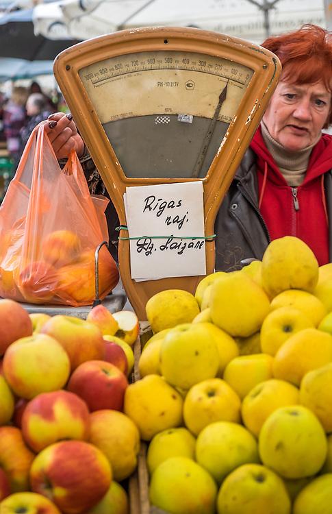 RIGA, LATVIA - CIRCA MAY 2014: Merchant selling apples in the Riga Central Market