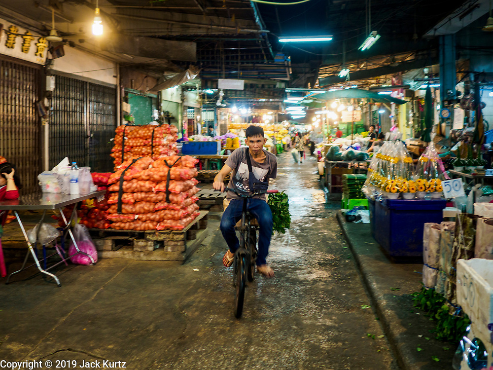 27 FEBRUARY 2019 - BANGKOK, THAILAND: A man pedals his bike through a part of the Bangkok flower market. Bangkok, a city of about 14 million, is famous for its raucous nightlife. But Bangkok's real nightlife is seen in its markets and street stalls, many of which are open through the night.        PHOTO BY JACK KURTZ