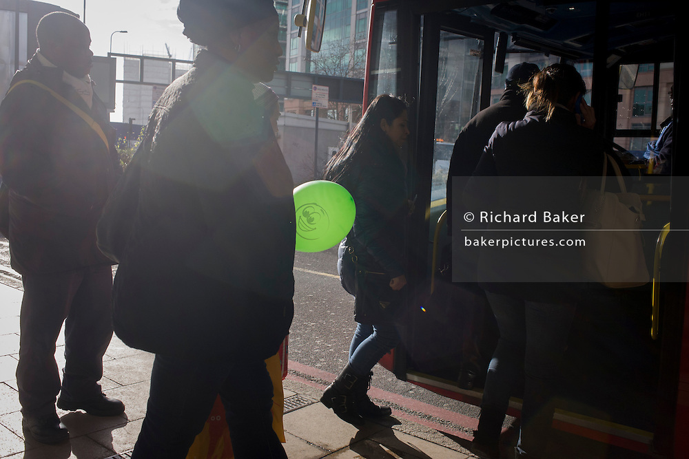 Passenger boards bus with green balloon at Vauxhall bus station, south London.
