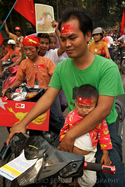 A father, despite his sleepy baby, does not renounce to take part in the parade. Mandalay, Myanmar. 2012