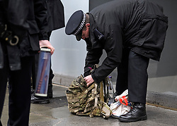 © Licensed to London News Pictures. 08/04/2018. London, UK. A police officer carrying what appears to be a weapon which was found in the possession of man who was arrested at an anti-semitism demonstration outside the headquarters of the Labour Party, in London. Labour party leader Jeremy Corbyn recently apologised for what he described as 'pockets' of anti-Semitism within Labour Party. Photo credit: Ben Cawthra/LNP