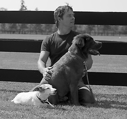 Man with two dogs looking off camera by a fence