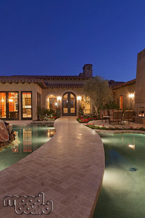 Open gate leading to luxury villa at dusk