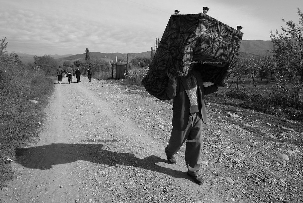 Villagers of Mereti fleeing the conflict zone, after their house were looted and partly burnt out. Mereti is located in the so called bufferzone between Gori and Tskhinvali, few days after the withdrawal of the russian forces from the area. The bufferzone was etablished after a short war in August 2008 as the georgian army assulted South Ossetia to overthrow the local separatist government.