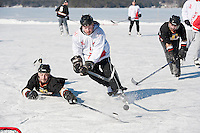 """The Locals"" Josh Houghton takes a shot on goal while O Do's Amber's Jarrod O'Donnell makes a diving attempt to block the puck during the semi final round of the New England Pond Hockey Classic Sunday afternoon.  The Locals advanced to the championship game against Broots Magoots to take the coveted cup trophy in the under 35 division.  (Karen Bobotas/for the Laconia Daily Sun)"