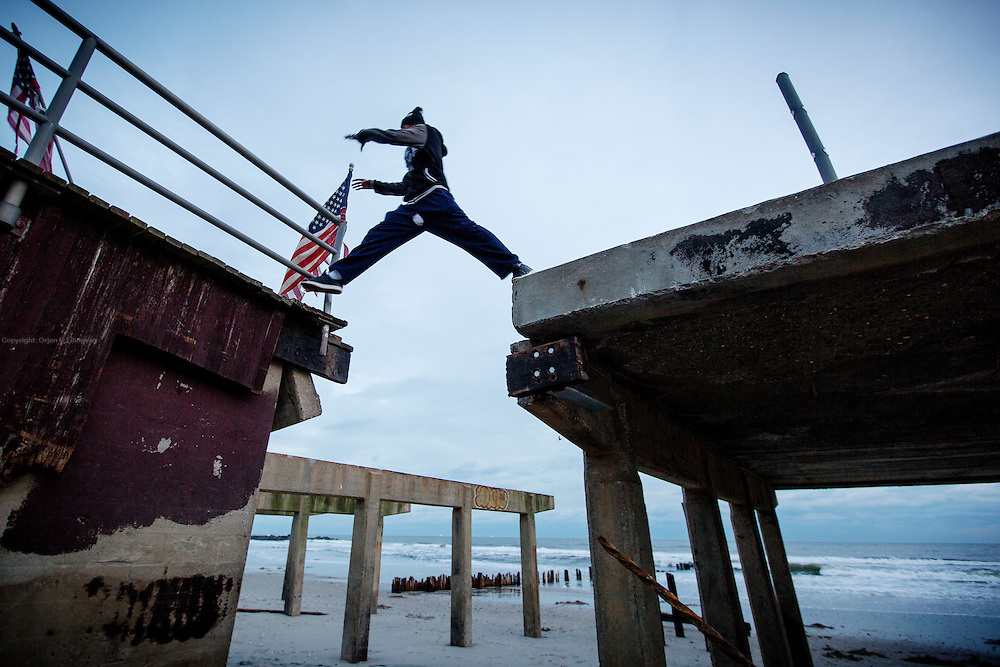 After Hurricane Sandy formed in the Atlantic Ocean, it killed at least 233 people in its path, crossing eight countries. In the picture, Jermaine Davis jumps between what was left of the boardwalk on Rockaway Beach. The material damages from the hurricane is estimated to have been about 75 billion dollars (US Department of Commerce May 2013). <br />