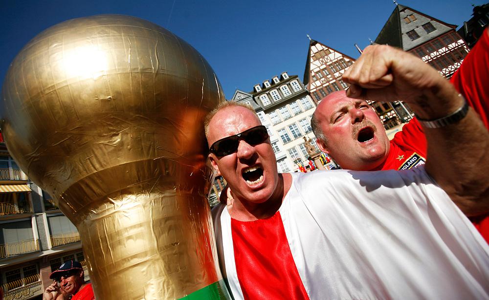Hanau | Deutschland 10.06.2006:  In der Innenstadt Frankfurts schauen englische Fu&szlig;ballfans das Spiel ihrer Mannschaft gegen Paraguay und feiern nachher den Sieg ihrer Mannschaft.<br /> <br /> hier: Englische Fans feiern den Sieg auf dem R&ouml;mer. Ein Fan hat einen gigantischen Weltmeisterschaftspokal gebastelt.<br /> <br /> Sascha Rheker<br /> 20060610<br /> <br /> [Inhaltsveraendernde Manipulation des Fotos nur nach ausdruecklicher Genehmigung des Fotografen. Vereinbarungen ueber Abtretung von Persoenlichkeitsrechten/Model Release der abgebildeten Person/Personen liegt/liegen nicht vor.]