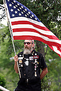 Member of the Patriot Guard Riders holding a US flag during the funeral service of Sgt. Ian T. Sanchez, in Staten Island, NY., on Tuesday, June 27, 2006. Sgt. Sanchez, a 26-year-old American serviceman was killed by a roadside bomb in the Pech River Valley, Afghanistan. The Patriot Guard Riders is a diverse amalgamation of riders from across the United States of America. Besides a passion for motorcycling, they all have in common an unwavering respect for those who risk their lives for the country's freedom and security. They are an American patriotic group, mainly but not only, composed by veterans from all over the United States. They work in unison, calling upon tens of different motorcycle groups, connected by an internet-based web where each of them can find out where and when a 'Mission' is called upon, and have the chance to take part. This way, the Patriot Guard Riders can cover the whole of the United States without having to ride from town to town but, by organising into different State Groups, each with its own State Captain, they are still able to maintain strictly firm guidelines, and to honour the same basic principles that moves the group from the its inception. The main aim of the Patriot Guard Riders is to attend the funeral services of fallen American servicemen, defined as 'Heroes' by the group,  as invited guests of the family. These so-called 'Missions' they undertake have two basic objectives in particular: to show their sincere respect for the US 'Fallen Heroes', their families, and their communities, and to shield the mourners from interruptions created by any group of protestors. Additionally the Patriot Guard Riders provide support to the veteran community and their families, in collaboration with the other veteran service organizations already working in the field.   **ITALY OUT**