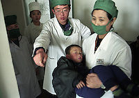 North Korea Eye Surgery Workshop. A boy is carried to pre operative examinations by a North Korean nurse before his cataract operation.