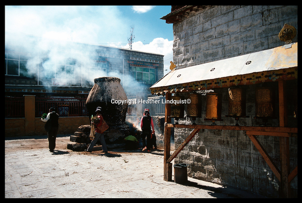 Tibetans make smoke offerings of Juniper in the large white chimea's during their circamumbulation of the Barkhor in Lhasa.