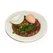 Ful medames an Egyptian breakfast dish of cooked faba beans eaten with bread or pita and onion often served with hard boiled egg