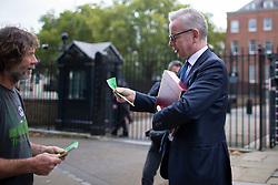 © Licensed to London News Pictures. 09/10/2019. London, UK. Chancellor of the Duchy of Lancaster Michael Gove reads a leaflet given to him by an Extinction Rebellion protester at the back of Downing Street. Police continue to attempt to clear roads on the third day of the protest . Photo credit: George Cracknell Wright/LNP