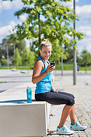 Portrait of young attractive woman sitting while using and listening to music on her smartphone in park