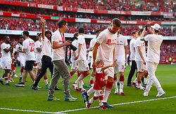 Arsenal's Aaron Ramsey celebrates on the pitch with his son after the final whistle