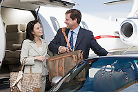 Mid-adult businesswoman and businessman getting in car.