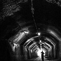 Man in old brick Tunnel, alone.  Light spills in from entrance at far end.