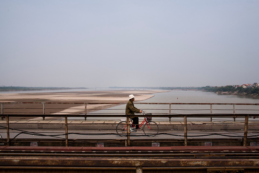 A cyclist rides across a secrtion of Long Bien Bridge with a view of the Red River behind him.