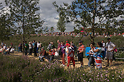 Spectators cheer on their favourite athletes surrounded by green grass and trees n the Olympic Park during the London 2012 Olympics. In the background are giant IOC Olympic rings on a hill. The planting of 4,000 trees, 300,000 wetland plants and more than 150,000 perennial plants plus  nectar-rich wildflower make for a colourful setting for the Games. This land was transformed to become a 2.5 Sq Km sporting complex, once industrial businesses and now the venue of eight venues including the main arena, Aquatics Centre and Velodrome plus the athletes' Olympic Village. After the Olympics, the park is to be known as Queen Elizabeth Olympic Park.