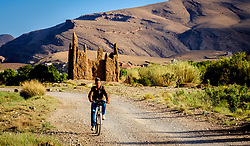 A young boy on a bicycle cycles passed a ruined Kasbah in the M'Guin Gorge in southern Morocco<br /> <br /> (c) Andrew Wilson | Edinburgh Elite media