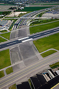 Nederland, Noord-Holland, Haarlemmermeer, 12-05-2009; luchthaven Schiphol met stationsgebouw en verkeertoren met vluchtleiding..Diagonaal naar het midden de C pier en rechts hiervan vertrekhal en aankomsthal. Rechts boven het midden ingang Schiphol Plaza (overdekt winkelcentrum). Op het middenplan parkeergarages en parkeerdekken, daar achter hotels en diverse kantoorgebouwen geexploiteerd door Schiphol vastgoed (Schiphol Real Estate). Aan de gates geparkeerde vliegtuigen van onder andere KLM. OSwart collectie, luchtfoto (toeslag); Swart Collection, aerial photo (additional fee required).foto Siebe Swart / photo Siebe Swart