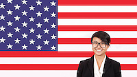 Portrait of young businesswoman smiling over American flag