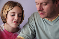 Single parent and young daughter working together,