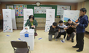 A woman casts a ballot as an official (R) of the National Election Commission looks on to declare close of ballot at a polling station for parliamentary elections in Seoul, South Korea, April 13, 2016. More than 24.4 million out of over 42.1 million, or 58 percent across South Korea gave their votes to elect new 300 lawmakers for the next four years, the National Election Commission said, according to local media.  Photo by Lee Jae-Won (SOUTH KOREA)  www.leejaewonpix.com