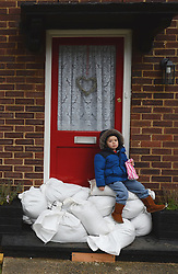 A local child sits on sand bags outside as floods hit Egham, United Kingdom, Wednesday, 12th February 2014. Picture by Andrew Parsons / i-Images