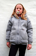 Girl wearing a grey hoodie with a dummy in her mouth