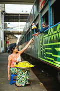 A woman on the platform selling snacks to passengers on a train before departure, Central Railway Station, Yangon, Myanmar