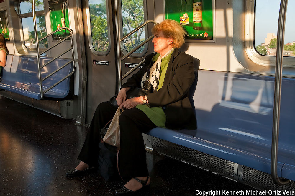 A woman on the N train heading towards the Ditmars Blvd. stop. The western light was streaming through the windows capturing her in a moment of introspection.