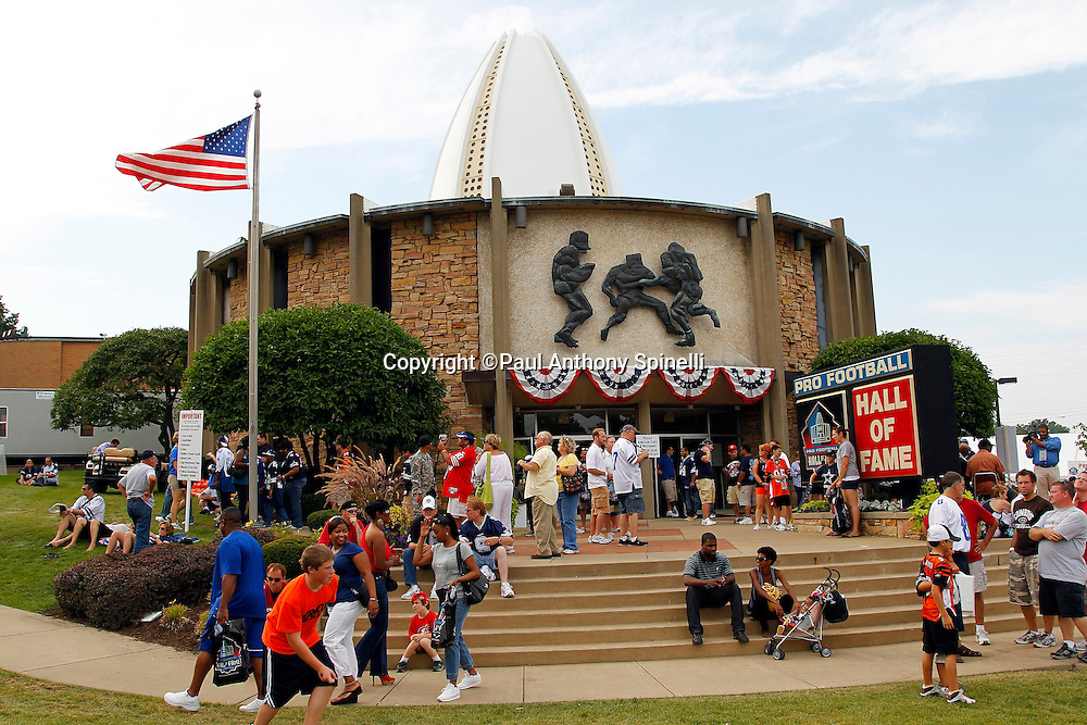 Fans walk the grounds in front of the Pro Football Hall of Fame prior to the NFL preseason football game between the Dallas Cowboys and the Cincinnati Bengals on Sunday, August 8, 2010 in Canton, Ohio. The Cowboys won the game 16-7. (©Paul Anthony Spinelli)