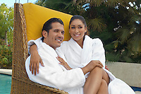 Couple in bathrobes relaxing in wicker chair by pool