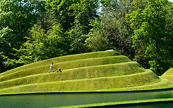 Wilkieston, Scotland, UK. 26 May 2020. Thomas Unterdorfer, Keeper of the Landscape at Jupiter Artland, cutting grass on the landform sculptures Cells of Life by Charles Jencks. Jupiter Artland hopes to have a limited opening in the near future when Covid-19 lockdown rules are relaxed. Iain Masterton/Alamy Live News
