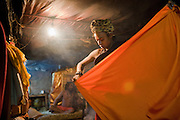 A young, Hindu sadhu, or wandering holy man, folds a traditional garment in a smoky temple room that is part of the Pashupatinath temple complex on May 12, 2008, in Kathmandu, Nepal (David Stubbs / Aurora)