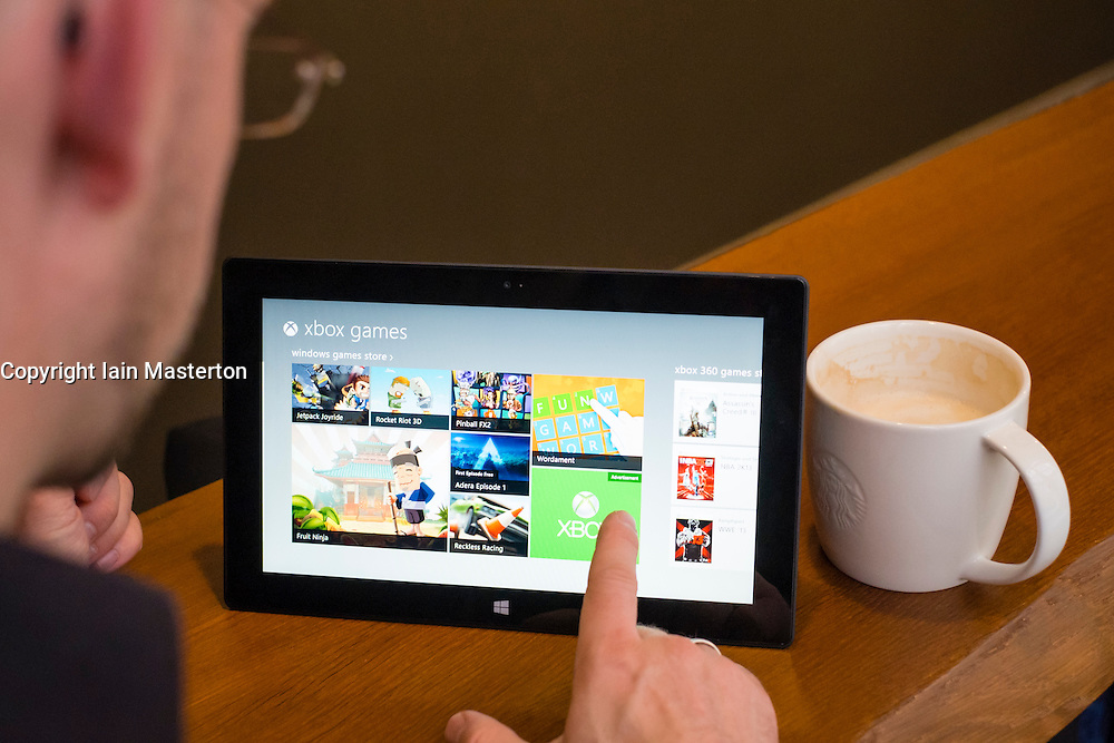 Man browsing Xbox games store on a Microsoft Surface rt tablet computer in a cafe