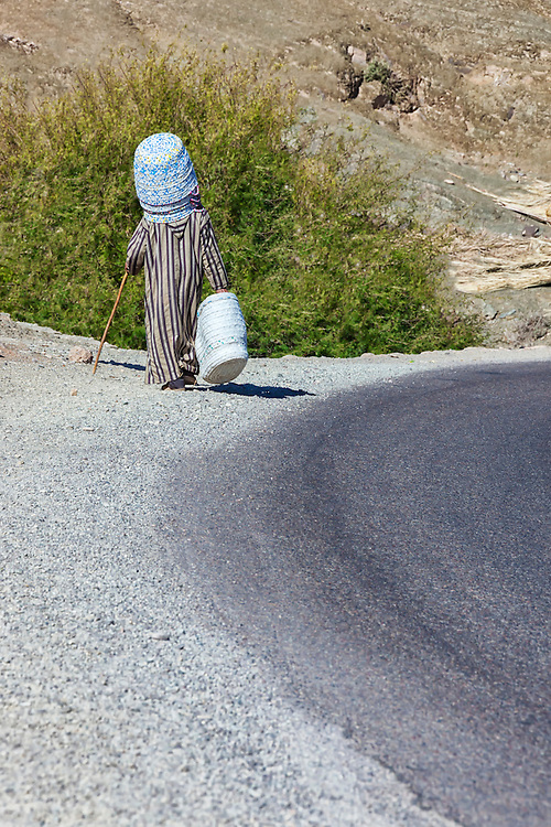 Old man walks near the road carrying baskets to sell.