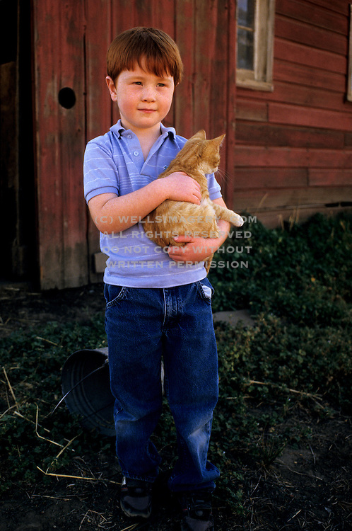 Image of a young farm boy and his cat, Waitsburg, Palouse, eastern Washington, Pacific Northwest, model released