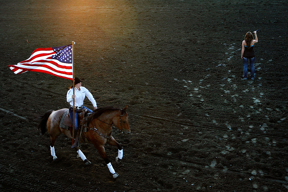 Alyssa LoParco of Kennewick sings the national anthem as Tia Trump gallops around the area with the flag on the first day of the Horse Heaven Round-Up in Kennewick, Wash. on Aug. 25, 2010.
