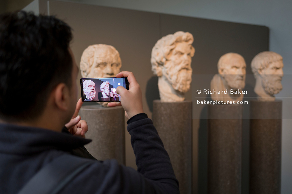 Visitors admire the heads of ancient Greek Hellenistic philosophers (L-R): Sokrates, Antisthenes, Chrysippus and Epikouros, in the British Museum, on 11th April 2018, in London, England.