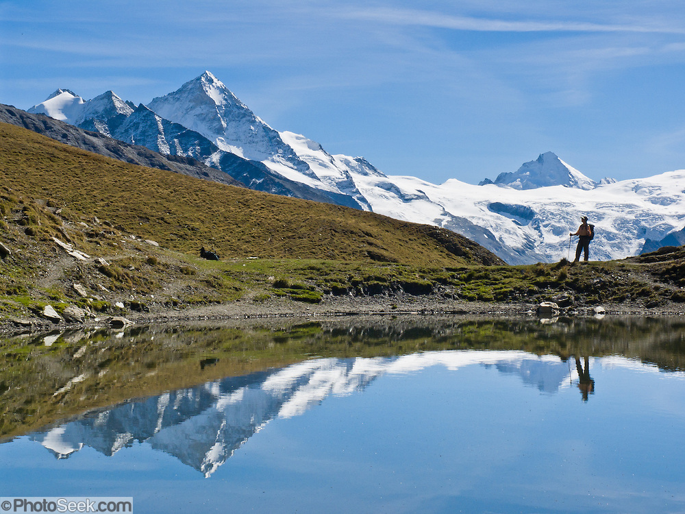 Dent Blanche (14,291 feet) and a trekker reflect in a pond in Val d'Hérens below Col du Torrent, Valais (Wallis) canton, Switzerland, on the High Route (Chamonix-Zermatt Haute Route), Pennine Alps, Europe.