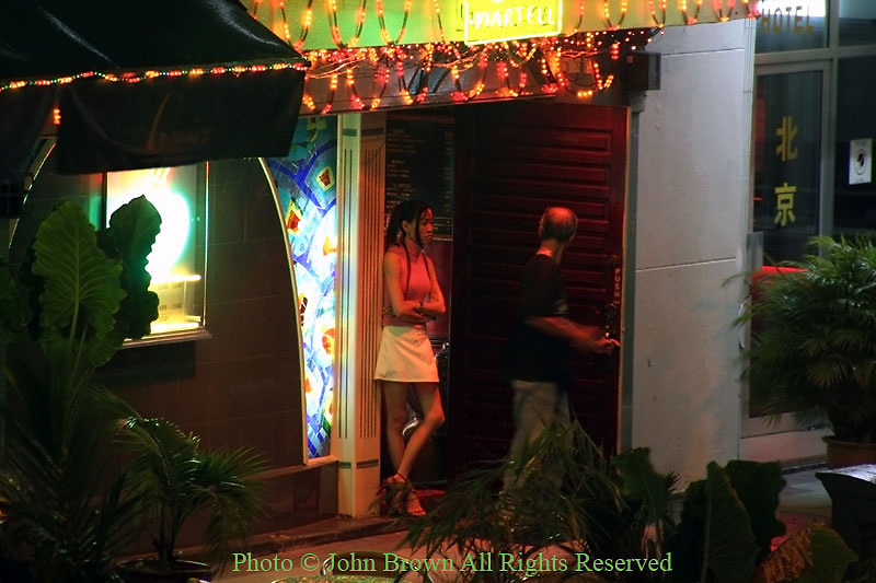 A bar hostess is watching a male customer leave a colorful cocktail lounge in Georgetown, Penang, Malaysia.