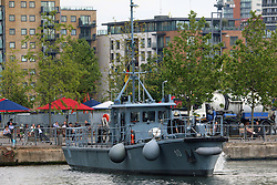 © Licensed to London News Pictures. 15/05/2014. Workers at Canary Wharf were surprised to see a flotilla of Germany Navy vessels appear outside their offices today. The port visit to London by the German Navy includes two mine sweepers (Siegburg and Auerbach), four remotely controlled drone ships, a refueling ship and more. The vessels will remain at West India Dock for the weekend. Workers enjoy the sun at lunchtime as a remote controlled drone minesweeper passes. Credit : Rob Powell/LNP