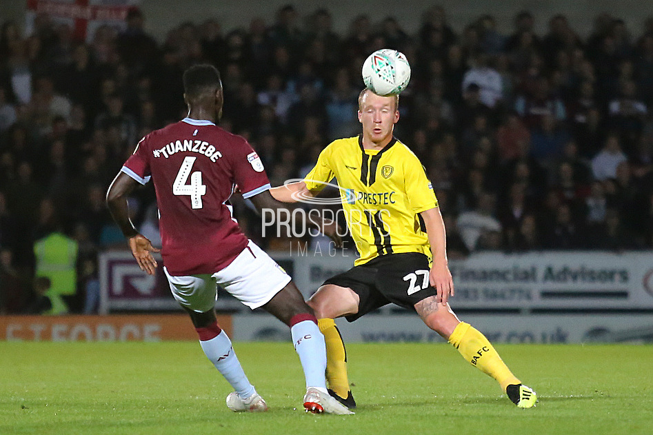 Aston Villa defender Axel Tuanzebe (4) on loan from Manchester United and Burton Albion forward Liam Boyce (27) during the second round or the Carabao EFL Cup match between Burton Albion and Aston Villa at the Pirelli Stadium, Burton upon Trent, England on 28 August 2018.